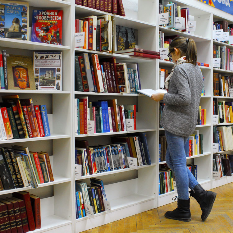 Woman examines books in retail store
