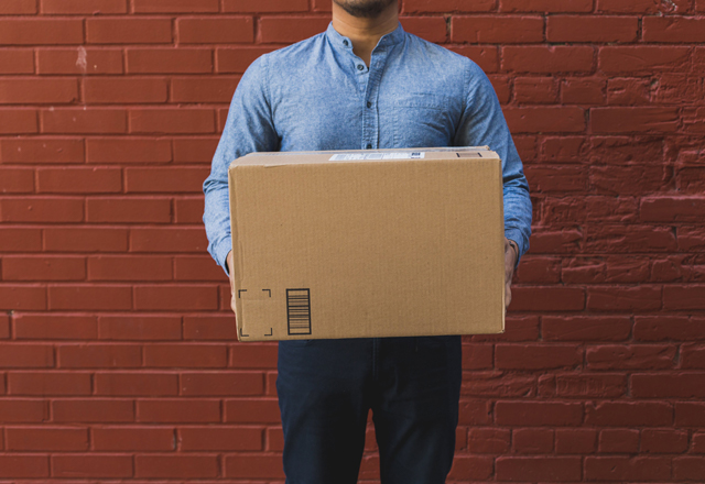 person in front of brick wall in denim shirt holding medium cardboard box