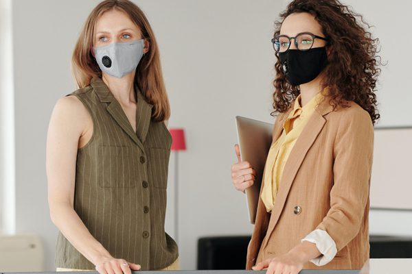 two businesswomen wearing face masks, facing each other looking the same direction.