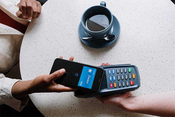 person pays for coffee with card app on phone | covid related retail transformation