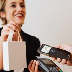 smiling saleswoman holds gift bag and pay device up for person holding their phone above it to pay