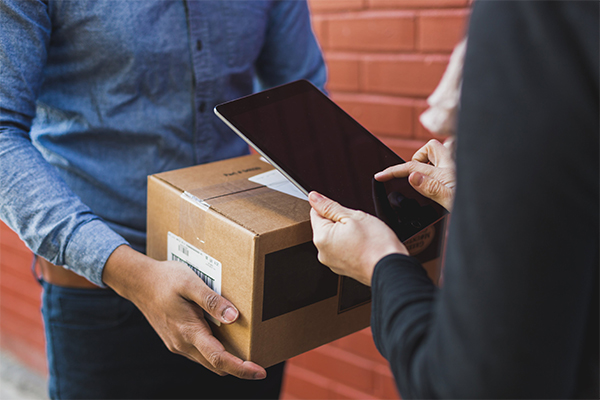 person signing for delivery on ipad over a box that a delivery person wearing a denim shirt is holding