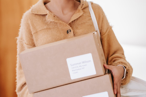 person in fuzzy brown sweater holding two smaller boxes