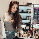 Happy beautiful Asian girl smiling young girl buys perfume cosme