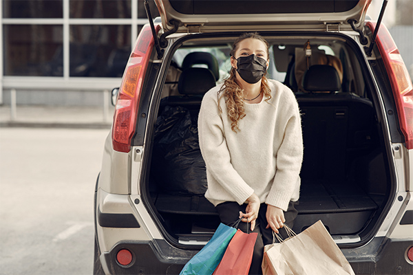 curbside fulfillment - girl  wearing mask holding shopping bags sitting against her open trunk
