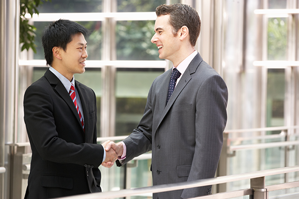 two businessmen shaking hands - DTC brands impact traditional retail and it's mutually beneficial