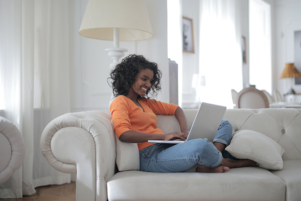 dark skinned woman with big short curls wearing orange shirt shopping on laptop on couch, DTC brands impact traditional retail - teaching big box stores about online marketing