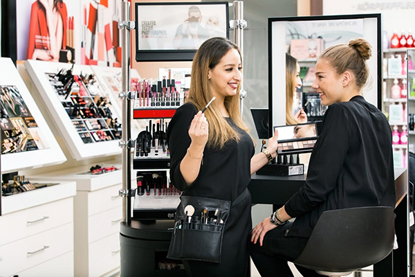 A sales associate is giving makeup tips to a customer in a Douglas store.