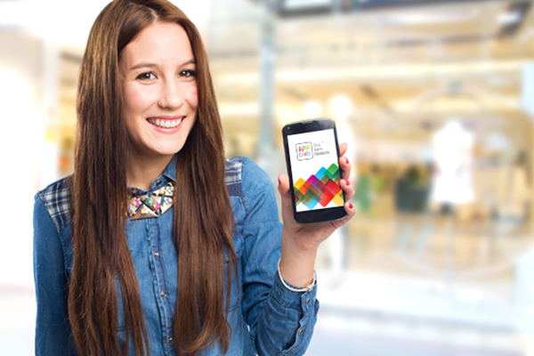 AppCard Retail Pro on smartphone being held up by smiling girl in a mall