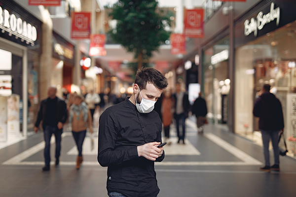 man wearing face mask in mall looking at his smart phone