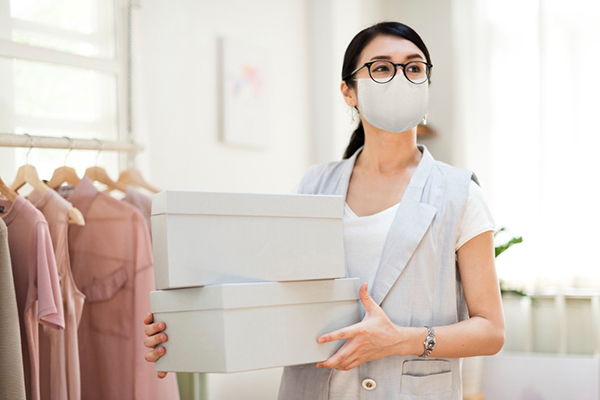 female asian shopkeeper looking up & out, wearing face mask and carrying two shoe boxes