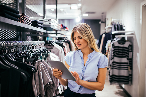 shopkeeper lady looks at tablet while in an aisle of hangers in store