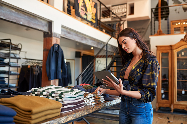 shopkeeper checks inventory on mobile device while thumbing through a stack of shirts
