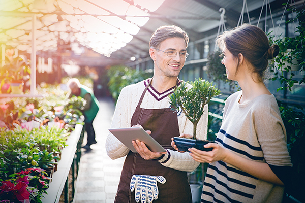 woman shopper holding plant smiling at male worker holding a tablet POS omnichannel strategies