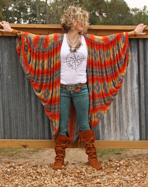 Blonde woman with short curly hair and warms extended wearing a colorful shawl, white tanktop, jeans and rustic leather boots