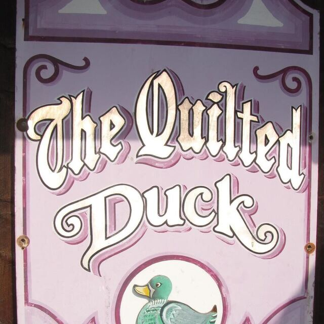 Logotype for The Quilted Duck in large, caligraphy-esque light violet colors