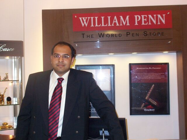 Cleanshaven Indian man in business suit standing inside store