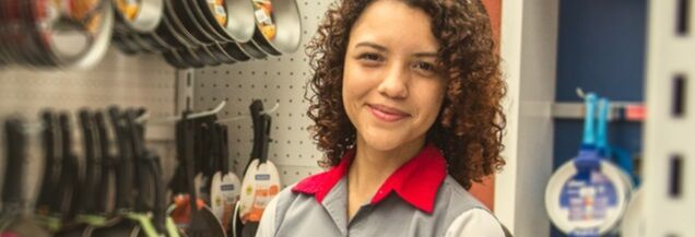 Woman store associate with brown curly hair wearing a grey collared shirt with bright red collars.