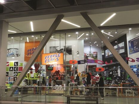 Exterior view of a large People Play's store with logo hanging from the cieling